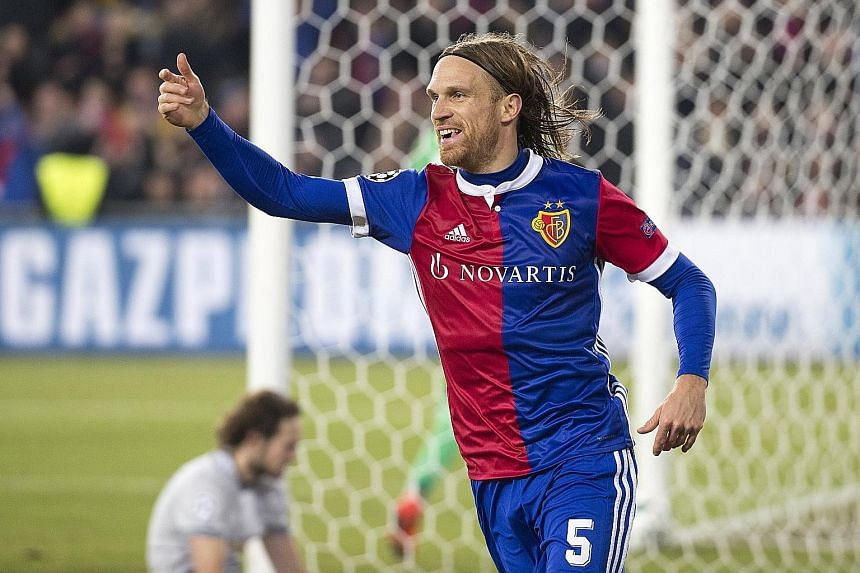 Left: Basel's Renato Steffen competing with Manchester United midfielder Paul Pogba on Wednesday. The Swiss club saw more of the ball once the Frenchman went off in the 65th minute. Below: Basel's Michael Lang celebrating his 89th-minute goal. Despit