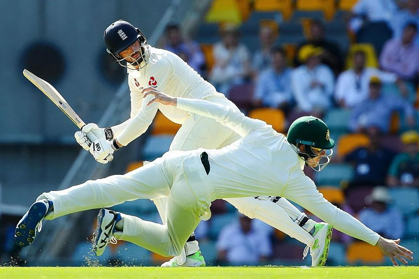 Australian fielder Cameron Bancroft diving as England batsman James Vince runs on the first day of the first cricket Ashes Test in Brisbane yesterday. Vince scored 83.