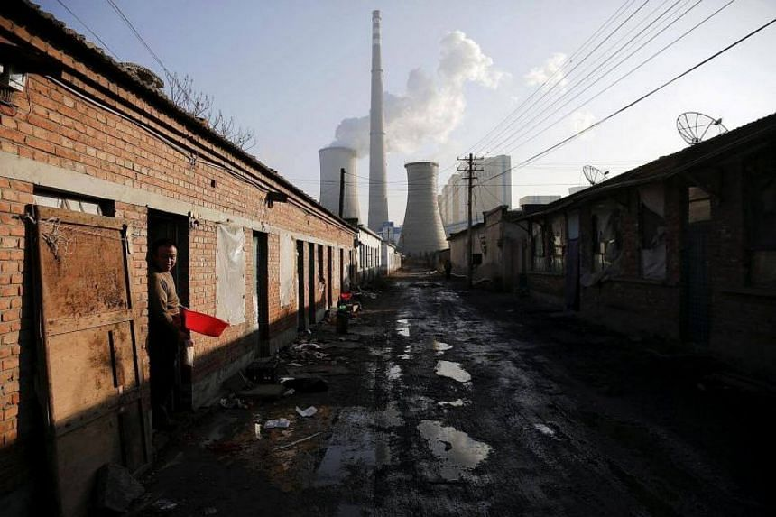 A file photo of a migrant worker stepping out of his accommodation in an area next to a coal power plant in Beijing during a smog-free day.