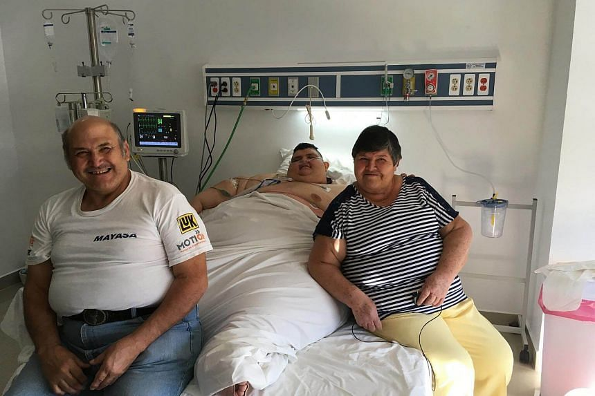 Mexican 32-year-old Juan Pedro Franco (centre) accompanied by his parents Herminio Franco (left) and Maria Salas at the intensive care room, where he recovers after an operation to reduce weight in Guadalajara, Mexico.