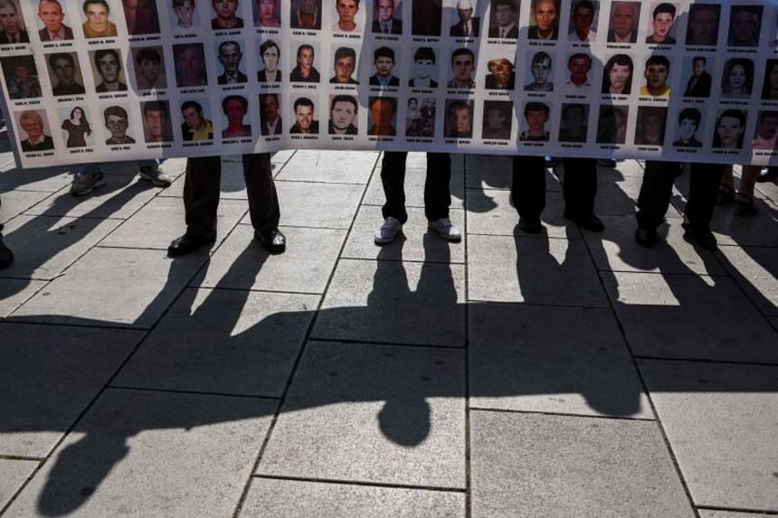 Kosovo Albanians hold a banner with the portraits of some of the missing people from the Kosovo war, during a ceremony to mark the International Day of the Disappeared in Pristina on Aug 30, 2017.