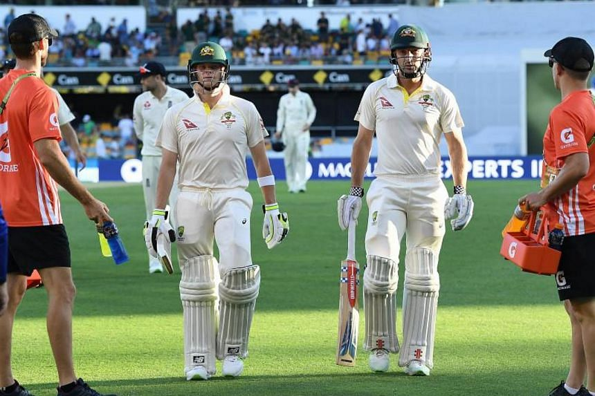 Australian captain Steve Smith (left) leaves the field with Shaun Marsh (right) on Day Two of the First Test match between Australia and England at the Gabba in Brisbane on Nov 24, 2017.