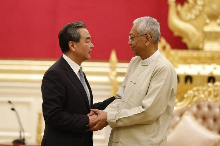 China's Foreign Minister Wang Yi (left), shakes hand with Myanmar's President Htin Kyaw (right) during their meeting at the Presidential House in Naypyitaw, Myanmar on Nov 19, 2017.
