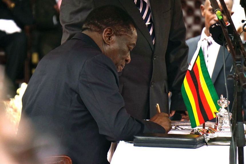 Newly sworn-in President Emmerson Mnangagwa signs a document during his inauguration ceremony at the National Sport Stadium in Harare on Nov 24, 2017.