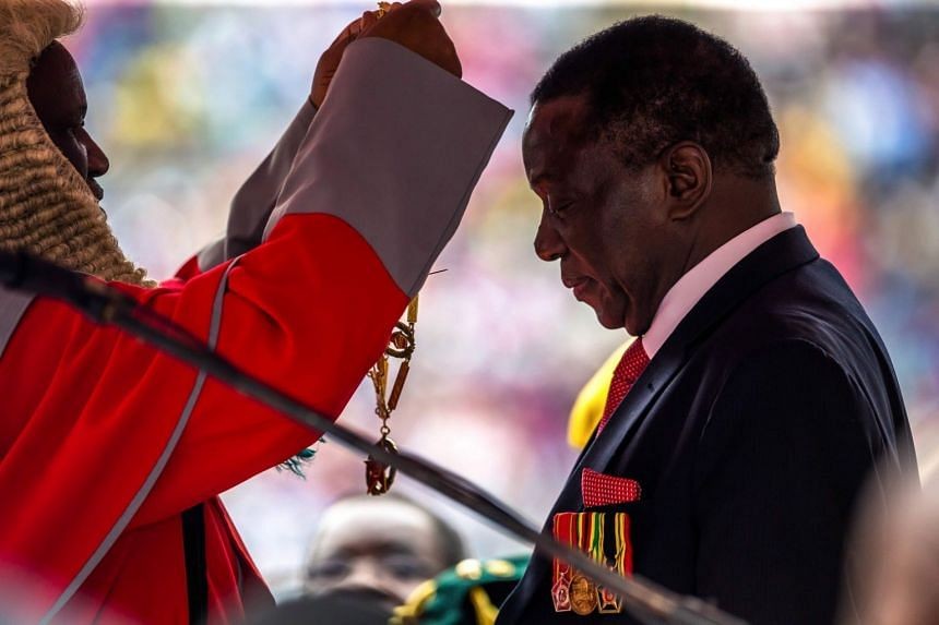 New Zimbabwean President Emmerson Mnangagwa receives the chain and sash of office from the chief judge of the Supreme Court, Chief Justice Luke Malaba, as he is officially sworn in.