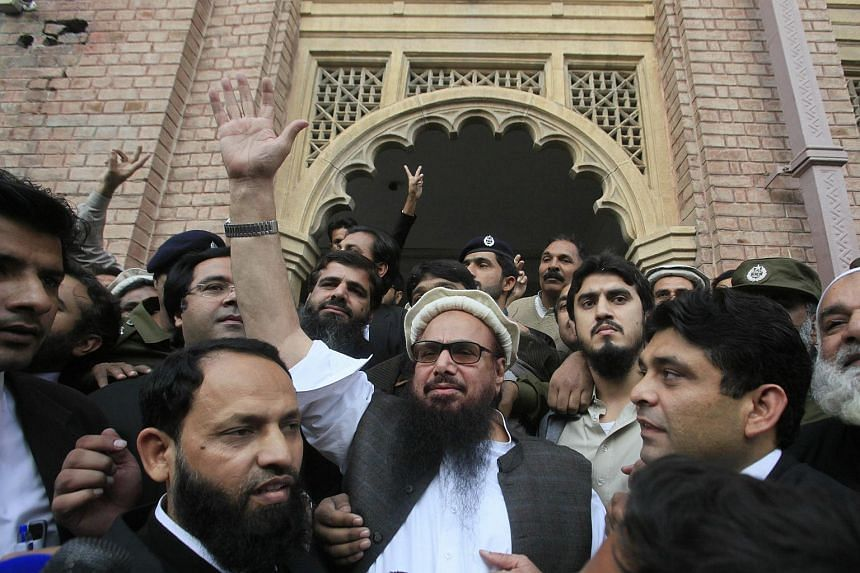 Hafiz Saeed (centre), the head of banned Islamic charity Jamat ud Dawa, waves to supporters after he was released by a court in Lahore, Pakistan on Nov 22, 2017.