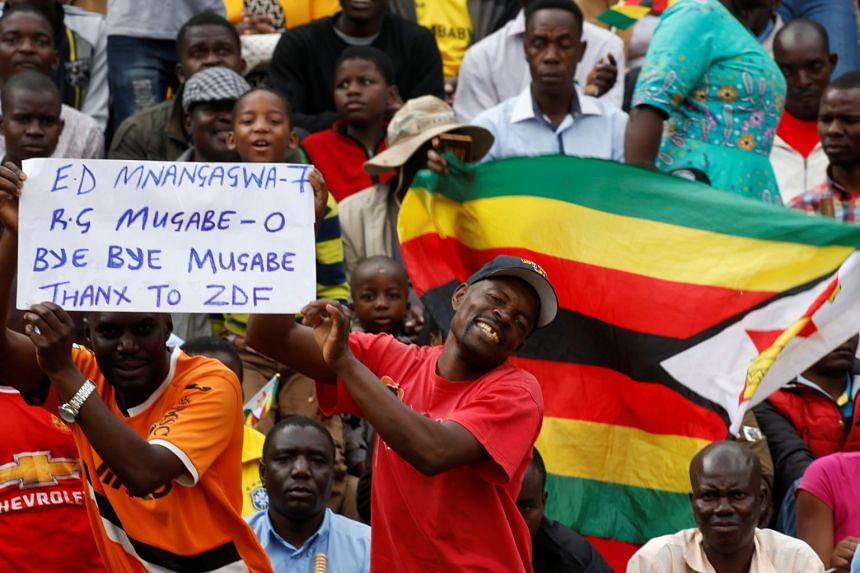 People wait for the inauguration ceremony to swear in Zimbabwe's former vice-president Emmerson Mnangagwa as president in Harare on Nov 24, 2017.