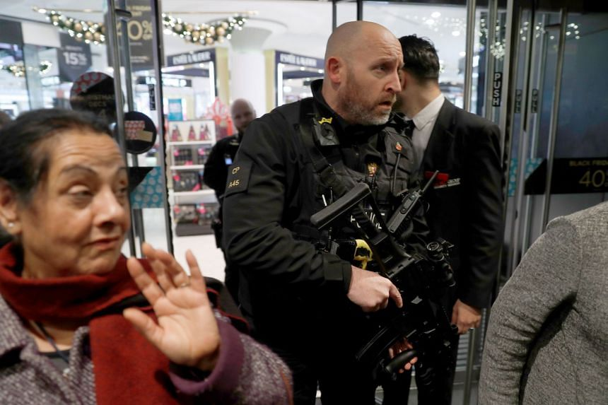Armed police officers mix with shoppers in an Oxford Street store, Nov 24, 2017.
