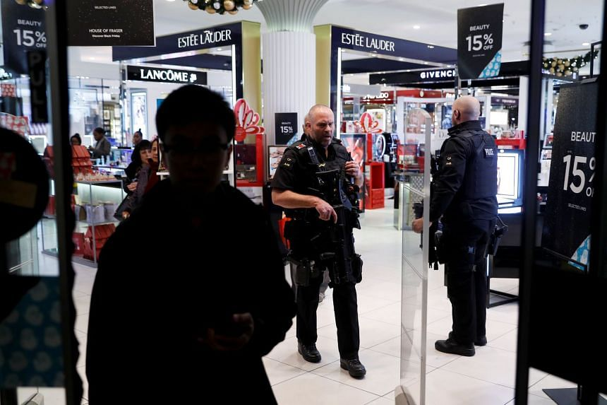 Armed police walk through a department store on Oxford Street.