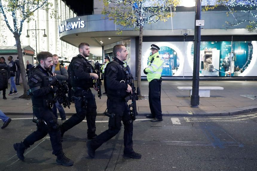 Armed police officers walk along Oxford Street.