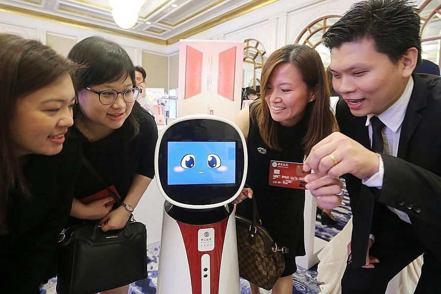 Bank of China's Singapore branch and SPH's Lianhe Zaobao launched the credit card yesterday at a ceremony featuring the bank's interactive robot.
