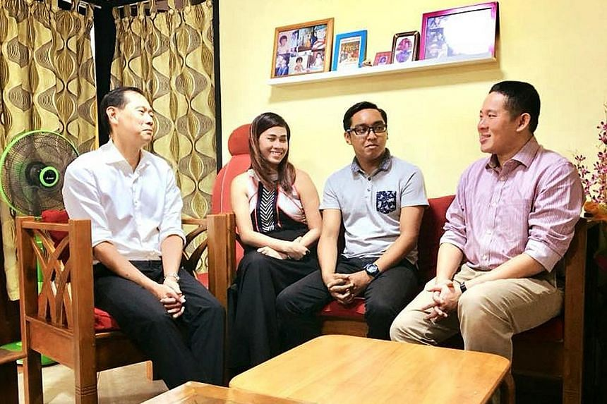 (From right) MP Amrin Amin with Traffic Police officer Khairulanwar Abd Kahar and his fiancee, Ms Rika, as well as Traffic Police Commander Sam Tee at Staff Sgt Khairulanwar's home yesterday.