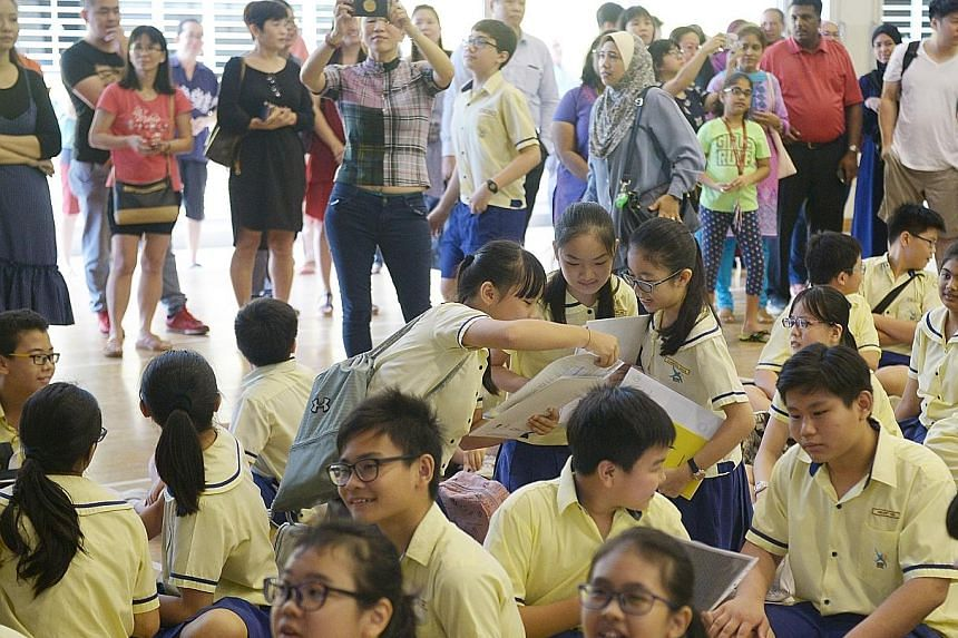 Pupils gathering at Lakeside Primary School to collect their PSLE results yesterday. Schools islandwide celebrated not only top performers, but also those who overcame the odds or did well in non-academic areas.