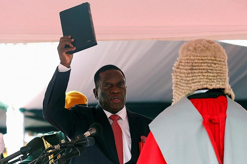 Mr Emmerson Mnangagwa being sworn in yesterday. He vowed to protect foreign investments and compensate farmers whose land was taken under a land redistribution programme initiated by former president Robert Mugabe.