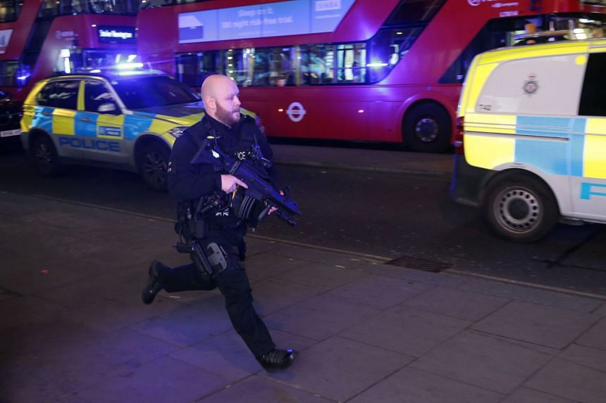 An armed policeman runs down Oxford Street as police responded to an incident.