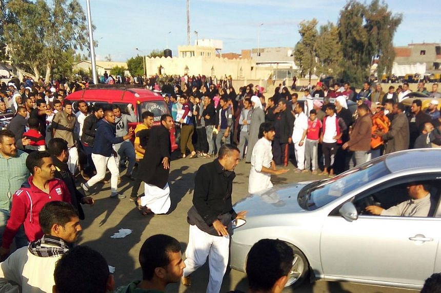 Egyptians gather at the site of a gun and bombing attack that targeted the Rawda mosque.