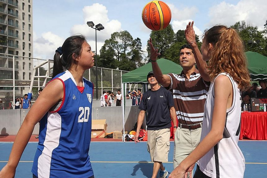 Sembawang GRC MP Vikram Nair, adviser to the constituency's grassroots organisations, tossing a basketball into the air to kick-start the finals of the girls' under-16 basketball competition yesterday. From dance-offs to playing sports, some 1,800 te