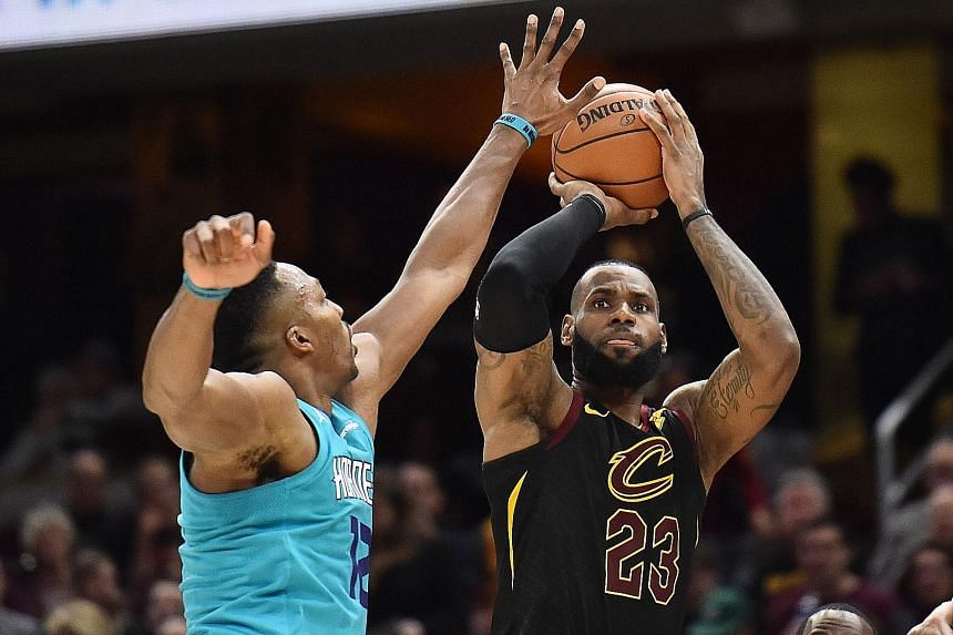 Cleveland Cavaliers forward LeBron James shoots over Charlotte Hornets centre Dwight Howard during the second half at Quicken Loans Arena. James finished with a triple-double as the Cavs won 100-99.