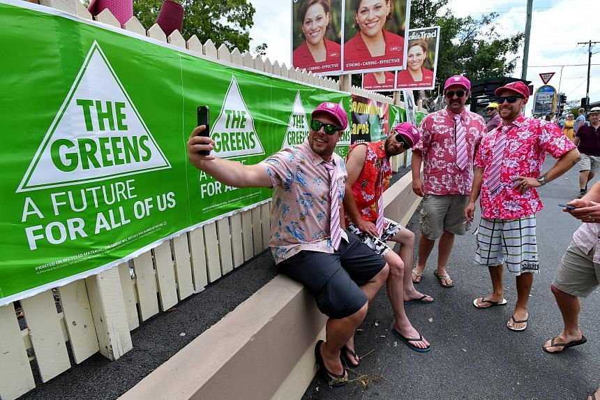 People posing for selfies outside a polling booth in Brisbane yesterday. Labor and the Greens performed strongly in big metropolitan areas in the south-east.