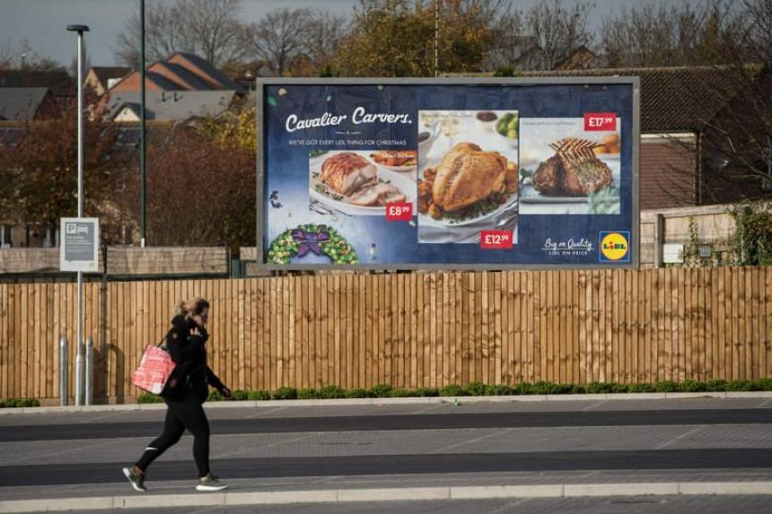 A woman walks past a billboard advertisement outside a branch of discount supermarket Lidl in central England on Nov 17, 2017.