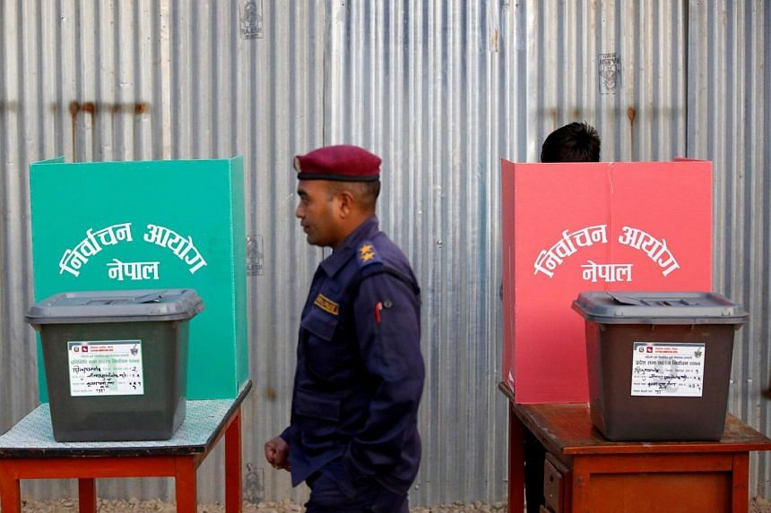 A police officer walks past ballot boxes at a polling station during the parliamentary and provincial elections in Nepal on Nov 26, 2017.