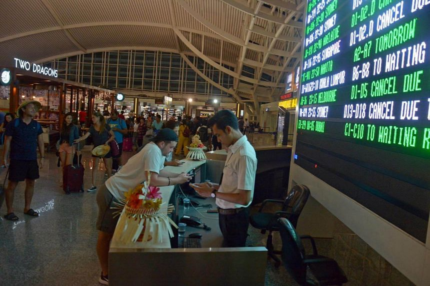 Passengers are seen waiting for flight information following the eruption of Mount Agung volcano at Ngurah Rai Airport in Bali.