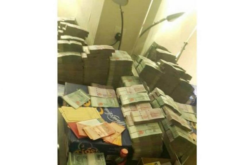 Some of the cash recovered by the Immigration Department during a raid at Kota Kinabalu hotel.