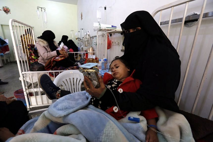 Yemeni women holding their malnourished children as they receive treatment at a hospital in Sana'a, on Nov 24, 2017.