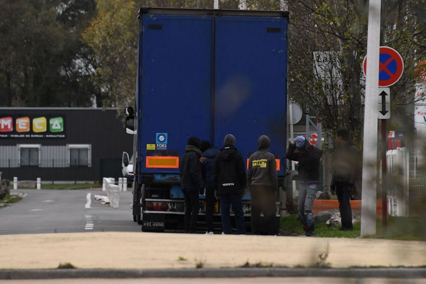 Migrants open the back doors of a lorry in Calais on Nov 14, 2017 in an attempt to reach England.