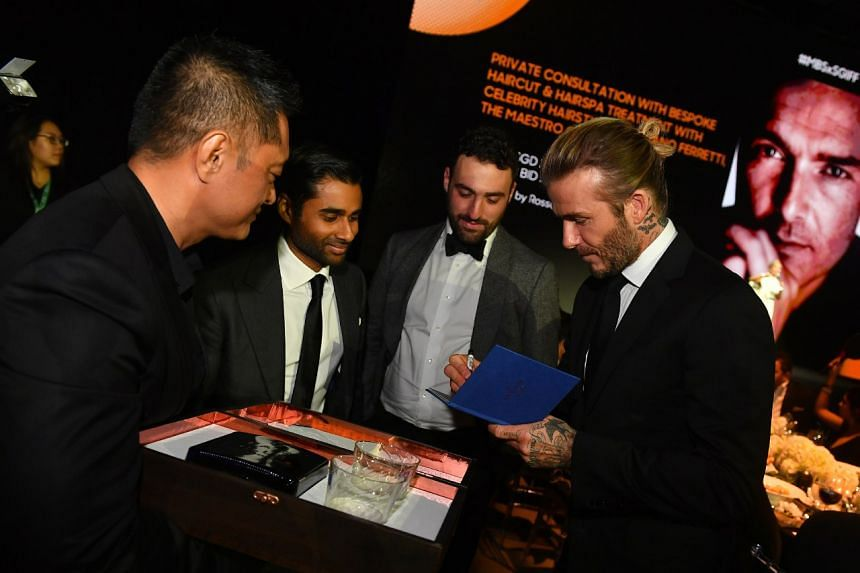 Beckham autographs his auction lot at the charity event.