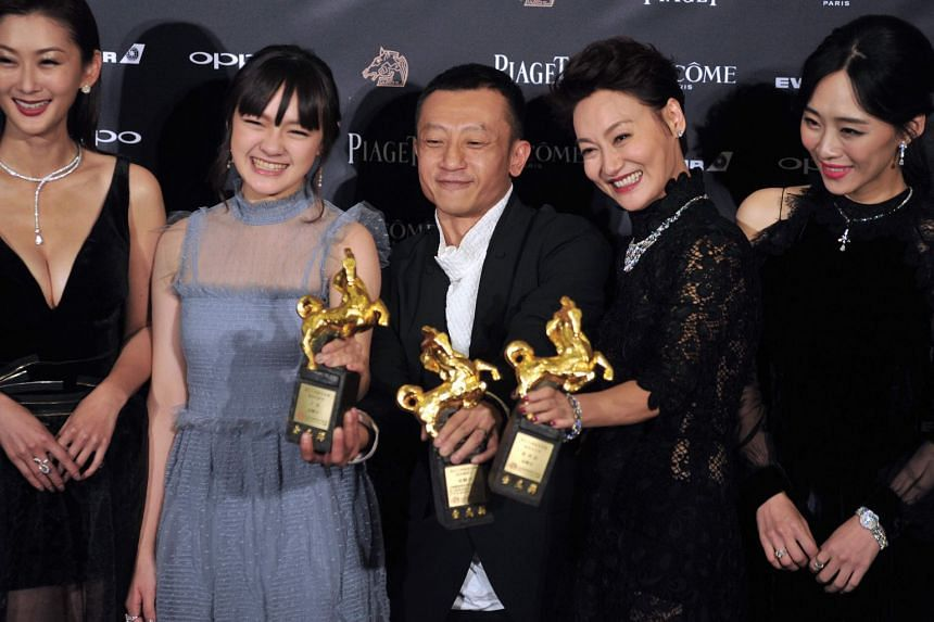 Taiwanese actress Vicky Chen (second left), Taiwanese director Yang Ya-che (centre) and actress Kara Hui Ying-hung (second right) (Kara Wai) pose with members of the cast after their film The Bold, The Corrupt, And The Beautiful won Best Feature Film