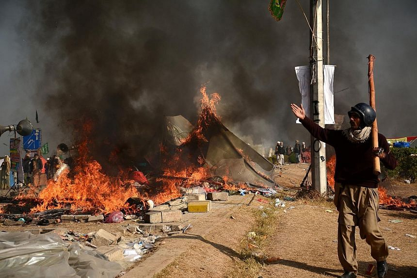 A protester in Islamabad seen near burning tents during clashes with police on Saturday.