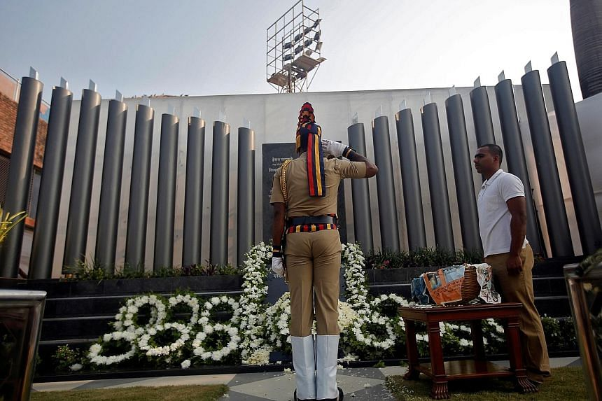 A policeman saluting at a police memorial marking the ninth anniversary of the attacks in 2008, which killed 166 people, in Mumbai, India, yesterday. Barricades were put up across the city and police deployed at every junction amid tightened security