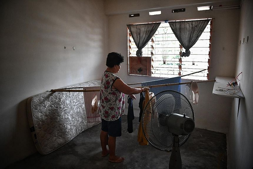Former hotel worker N.K. Yap, a resident of Stulang Darat, has set up a small gardening area of her own behind the estate. Children in the estate waiting for the bread van. When people hear the horn, those living on the higher floors lower baskets to