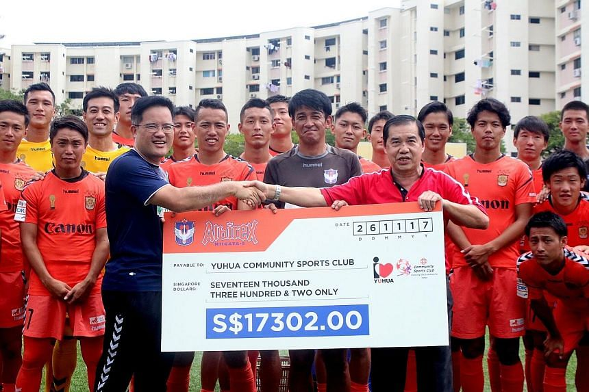 S-League champions Albirex Niigata vice-chairman Koh Mui Tee (in blue) presenting a cheque of $17,302 to Lim Chock Sing, chairman of Yuhua Community Sports Club, yesterday. It was to honour the fifth memorandum of understanding the Japanese club sign