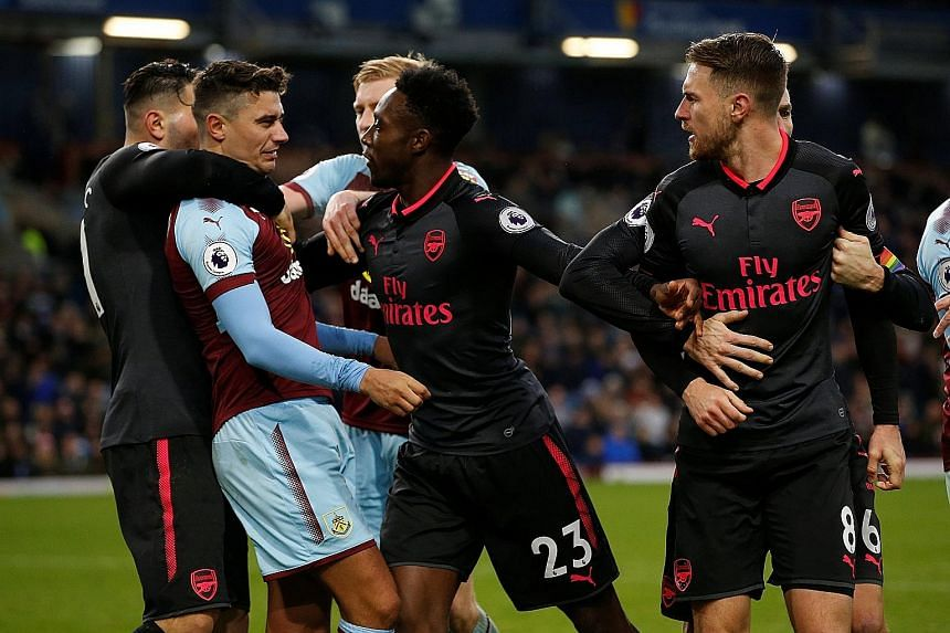 Arsenal's Danny Welbeck (No. 23) steps in to intervene after Burnley's Matthew Lowton clashed with Aaron Ramsey (No. 8) for the latter's part in winning the penalty deep into stoppage time. Arsenal's Alexis Sanchez celebrates after scoring the last-g