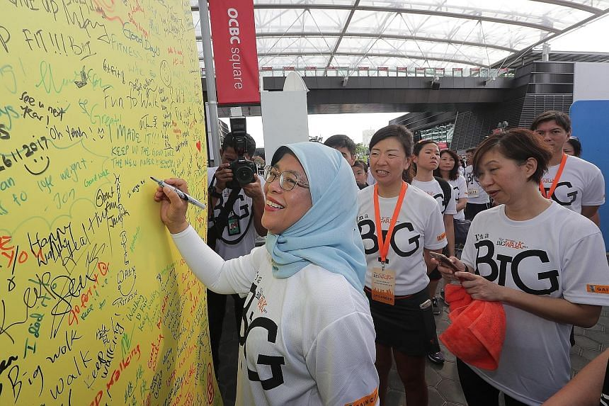 Above: President Halimah Yacob signing off on the National Steps Challenge pledge board yesterday, encouraging everyone to walk and exercise every day. Left: Participants in yesterday's Big Walk, which began and ended at the Sports Hub.