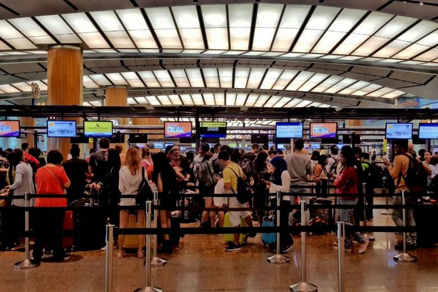 About 50 people affected by the cancellation of their flight to Bali wait in line at a Scoot counter in Changi Airport Terminal 2, to try to get on flights to other South-east Asian countries. ST PHOTO: LESTER HIO