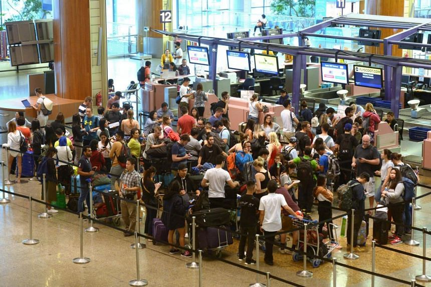 Travellers, whose flight to Bali was cancelled as a result of the Mount Agung eruption, lining up at a Scoot counter at Changi Airport Terminal 2.