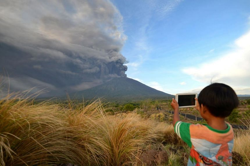 A boy takes pictures during Mount Agung's eruption seen from Kubu sub-district in Karangasem Regency on Indonesia's resort island of Bali on Nov 26, 2017.