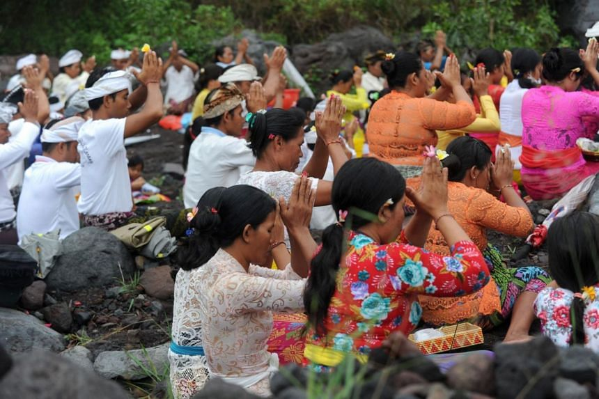 Balinese Hindus take part in a ceremony, where they pray near Mount Agung in hope of preventing a volcanic eruption, in Muntig village of the Kubu sub-district in Karangasem Regency on Indonesia's resort island of Bali on Nov 26, 2017.