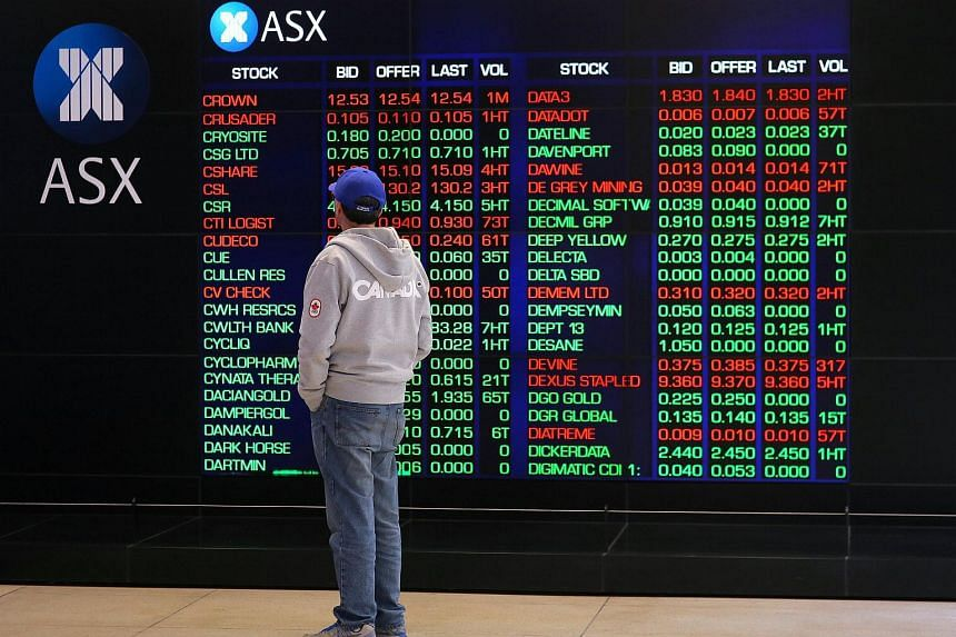 An investor looks at a board displaying stock prices at the Australian Securities Exchange (ASX) in Sydney.