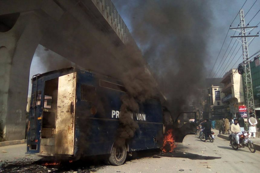 Pakistani residents walk past a burning prison van torched by protesters from the Tehreek-i-Labaik Yah Rasool Allah Pakistan (TLYRAP) religious group during clashes with police in Rawalpindi.