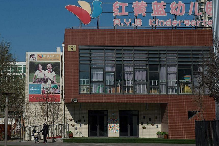 People leave the RYB Education New World kindergarten in Beijing on Nov 24.