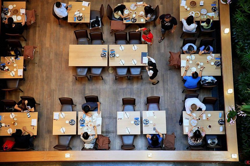 People dine in a restaurant at a mall in Singapore.