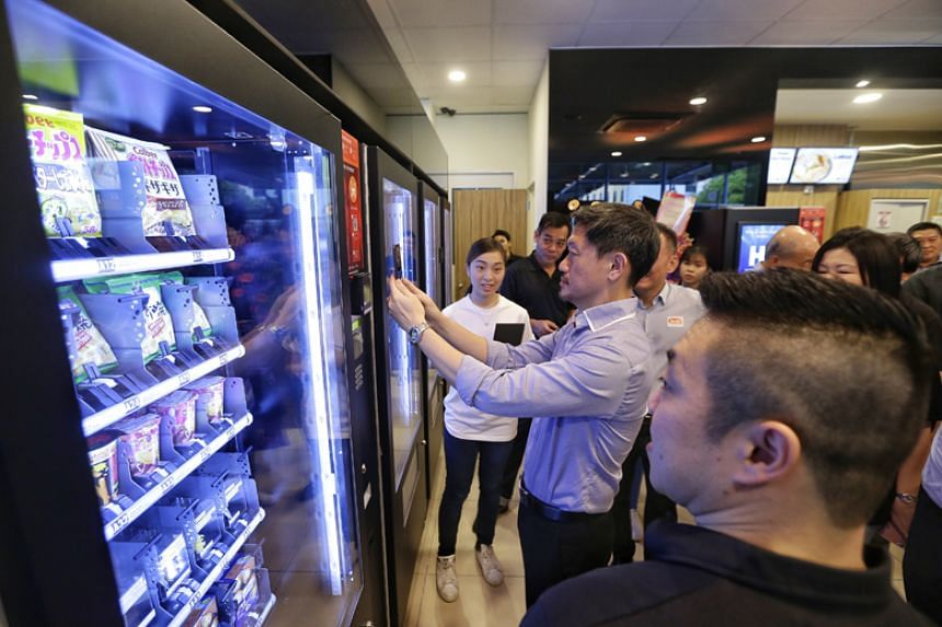 Singapore Press Holdings' deputy chief executive Anthony Tan checking out the cashless vending machine which dispenses Japanese snacks at the Cynergy Gas Station on Nov 27, 2017.
