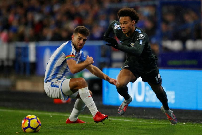 Manchester City's Leroy Sane in action with Huddersfield Town's Tommy Smith at John Smith's Stadium, Huddersfield, Britain on Nov 26, 2017.