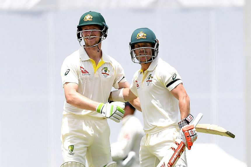 Australian batsmen David Warner (right) and Cameron Bancroft celebrate after Australia won on Day 5 of the First Test match between Australia and England at the Gabba in Queensland, Australia on Nov 27, 2017.
