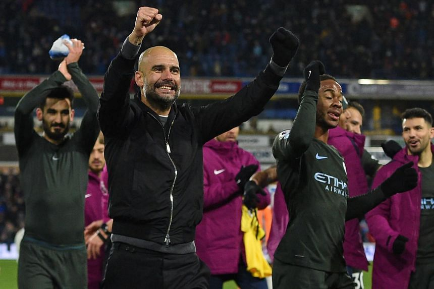 Manchester City's Spanish manager Pep Guardiola (second, left) celebrates with his players on the pitch after the English Premier League football match between Huddersfield Town and Manchester City at the John Smith's stadium in Huddersfield.