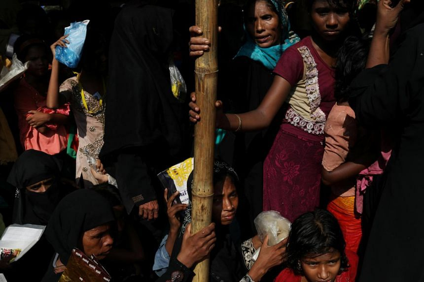 Rohingya refugees wait for the start of relief aid distribution at Balukhali refugee settlement, near Cox's Bazar, Bangladesh.